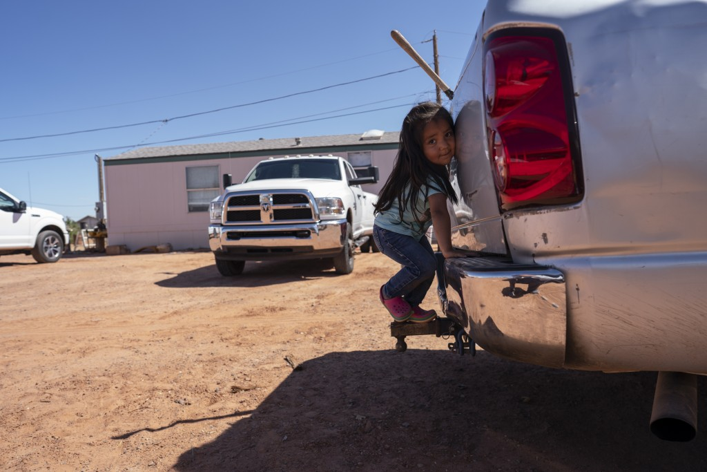 In this April 22, 2020, photo, a little girl plays in her family compound in Tuba City, Ariz. Even before the pandemic, people living in rural communi...