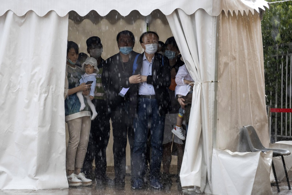 Visitors wearing masks to curb the spread of the coronavirus take shelter from a sudden rainstorm at a park in Beijing on Saturday, May 23, 2020. New ...