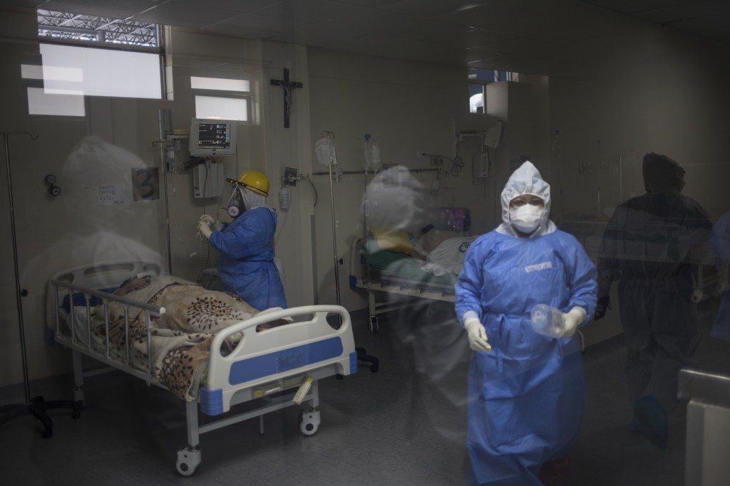 Doctors and nurses attend to COVID-19 patients inside the intensive care unit at the Guillermo Almenara hospital in Lima, Peru, Friday, May 22, 2020. ...