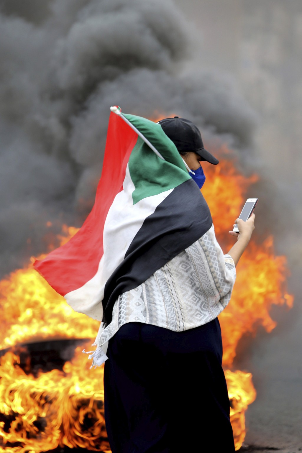 A Sudanese woman carries a national flag during a demonstration to commemorate the first anniversary of a deadly crackdown carried out by security for...