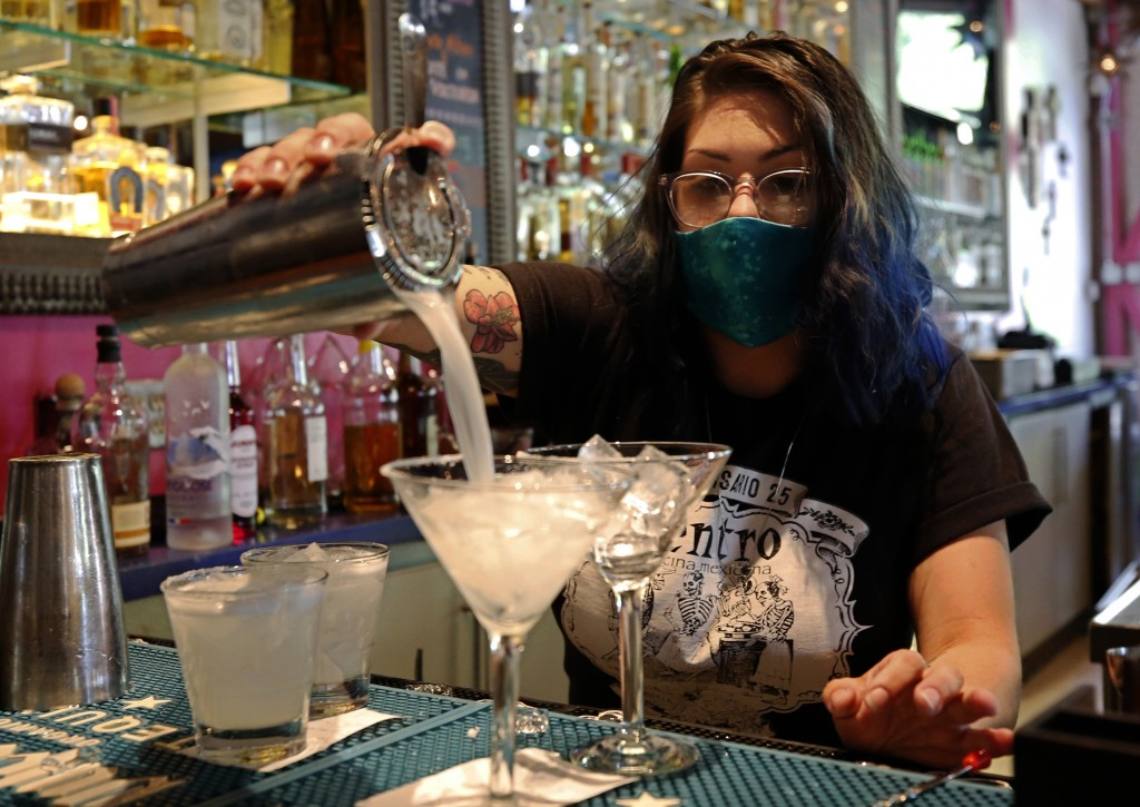 Bartender Taylor Osorio wears a face mask as she pours drinks at Centro Cocina Mexicana restaurant in Sacramento, Calif., Friday, May 22, 2020. As par...