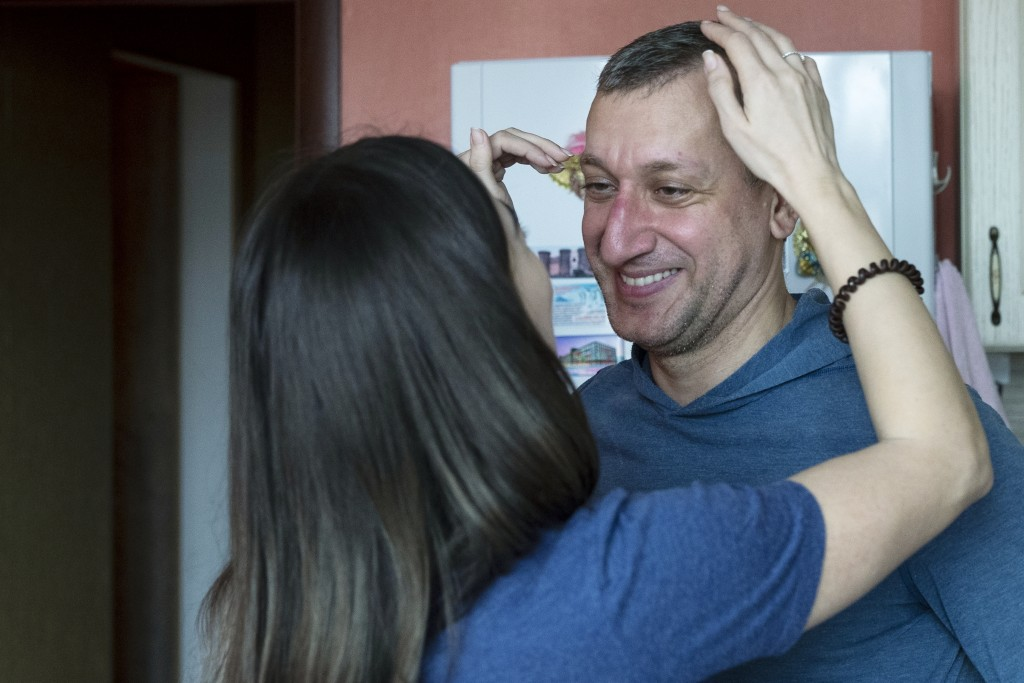 In this photo taken on Saturday, May 16, 2020, Dr. Osman Osmanov is greeted by his wife Saida after a shift at an intensive care unit of Filatov City ...