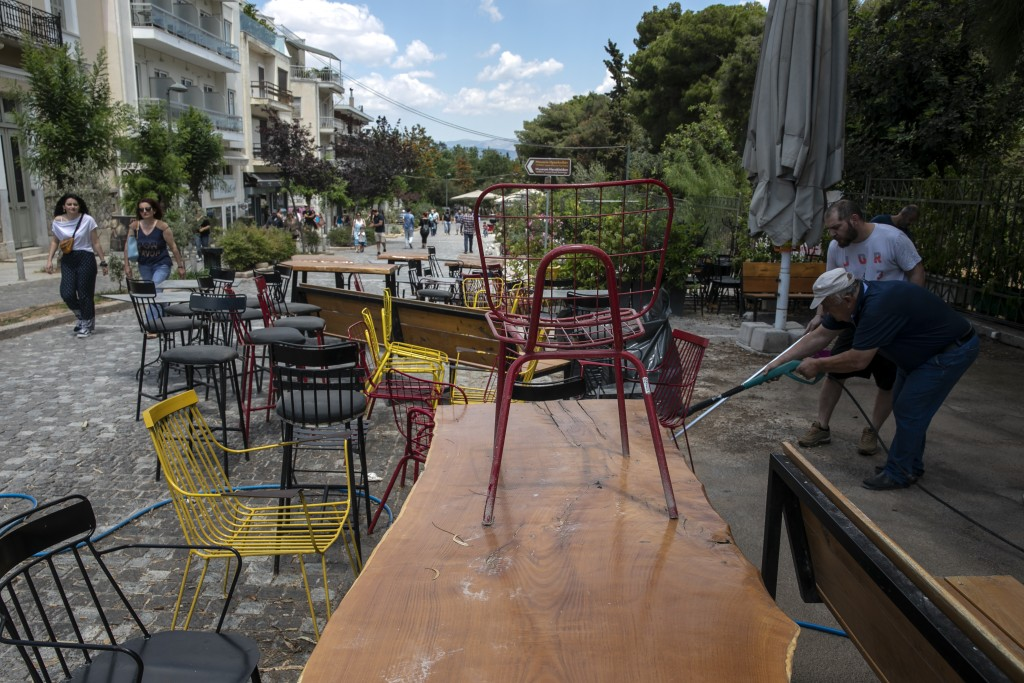 Employees clean the exterior of a coffee shop as they prepare for reopening, in Athens, on Saturday, May 23, 2020. Restaurants and cafes are allowed t...