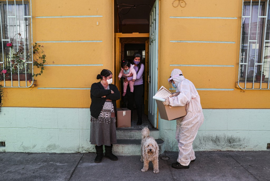 A city worker, dressed in protective gear, delivers a box of food during a mandatory quarantine ordered by the government amid the new coronavirus pan...