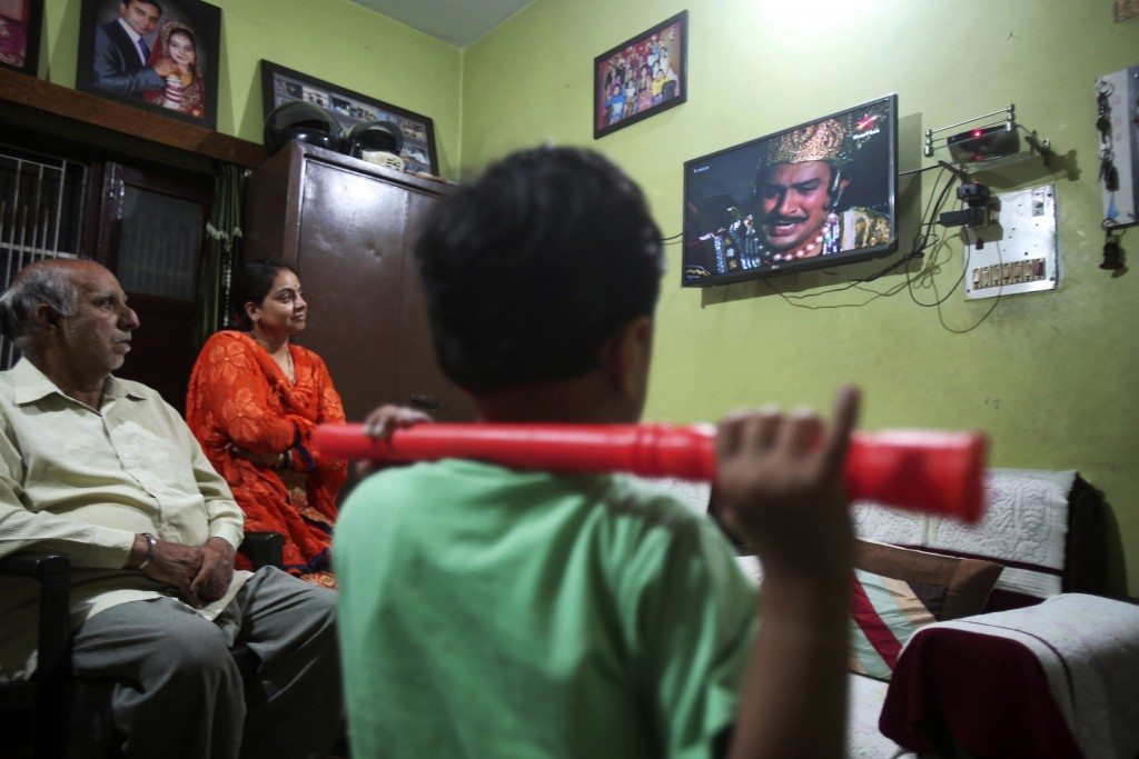 """An Indian family watches epic television series """"Ramayan"""" at their home in Jammu, India May 18, 2020. The country's public broadcaster last month revi..."""