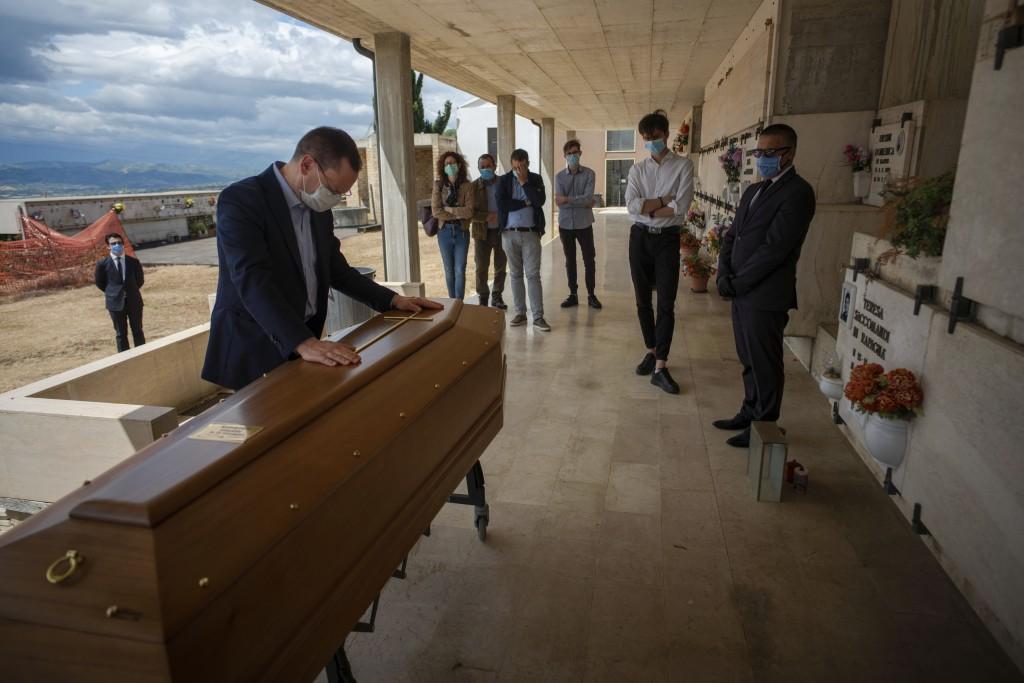 Sabatino Di Girolamo, mayor of Roseto degli Abruzzi, left, touches the casket containing the body of his mother, Annunziata Ginoble, before her inhuma...