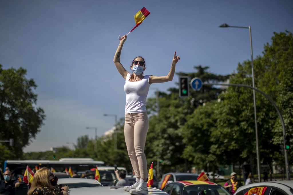 A woman waves a Spanish flag during a drive-in protest organised by Spain's far-right party Vox against the Spanish government's handling of the natio...