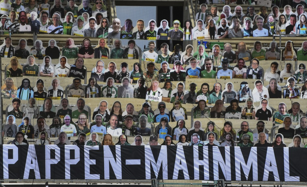 "A banner reading ""cardboard memorial"" is placed next to cardboard pictures of fans ahead the German first division Bundesliga football match Borussia ..."