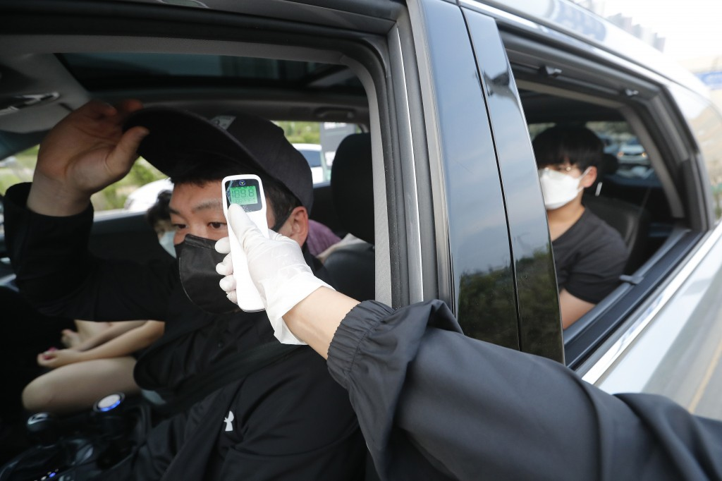 A man in a car receives a body temperature check as he arrives to watch the Stage X drive-in concert at KINTEX parking lot in Goyang, South Korea, Sat...