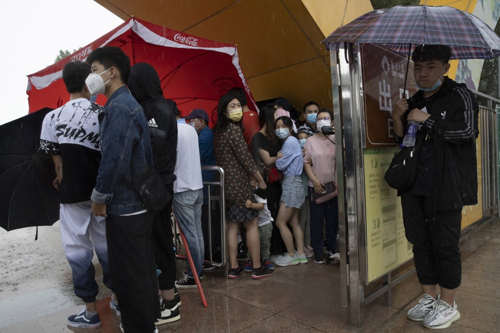 Visitors wearing mask to curb the spread of the coronavirus takes shelter from a sudden rainstorm in Beijing on Saturday, May 23, 2020. New coronaviru...