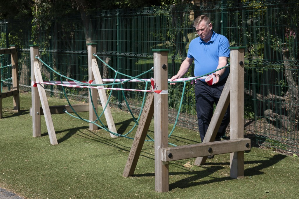 Head teacher Graham Hamilton tapes off playground equipment as measures are taken to prevent the transmission of coronavirus before the possible reope...