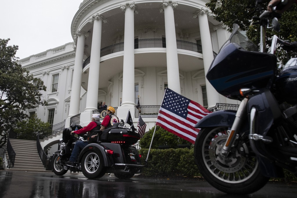 """President Donald Trump watches riders from the Blue Room Balcony of the White House, during a """"Rolling to Remember Ceremony,"""" to honor the nation's ve..."""