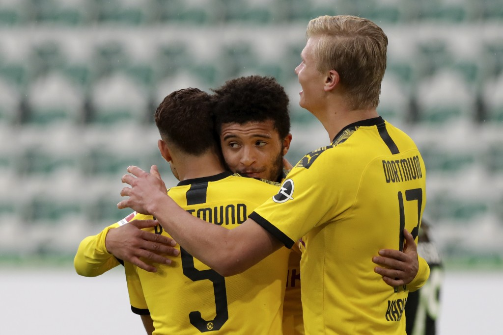 Dortmund's Achraf Hakimi, left, celebrates with Jadon Sancho and Erling Haaland, right, after scoring his side's second goal during the German Bundesl...