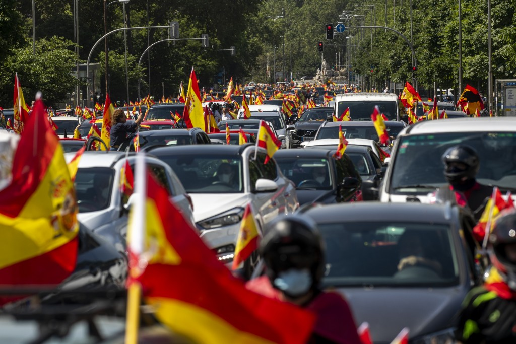 People wave Spanish flags during a drive-in protest organised by Spain's far-right Vox party against the Spanish government's handling of the nation's...