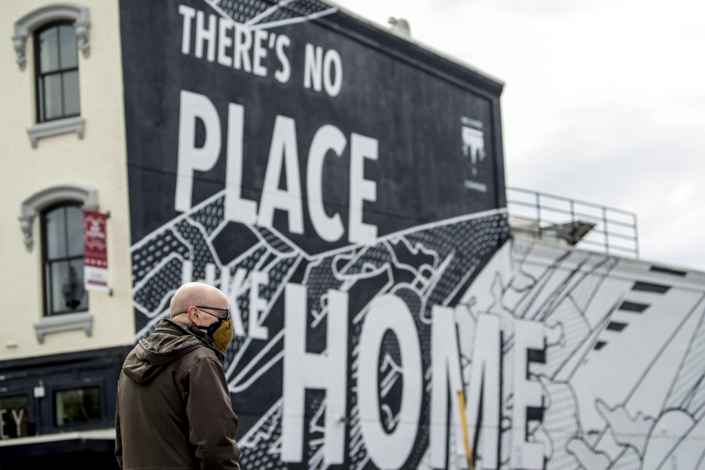 "FILE - In this April 14, 2020, file photo, a mural that reads ""There's No Place Like Home"" is visible as a man wearing a mask crosses 14th Street in W..."