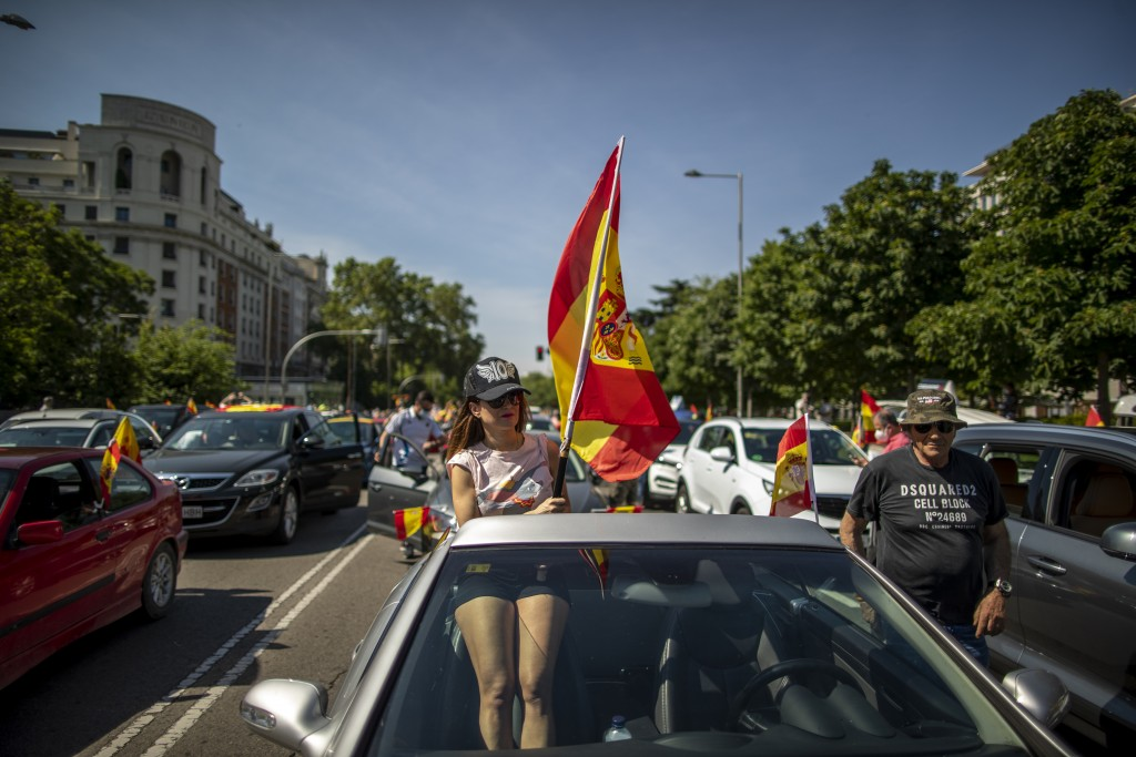 A woman waves a Spanish flag during a drive-in protest organised by Spain's far-right Vox party against the Spanish government's handling of the natio...