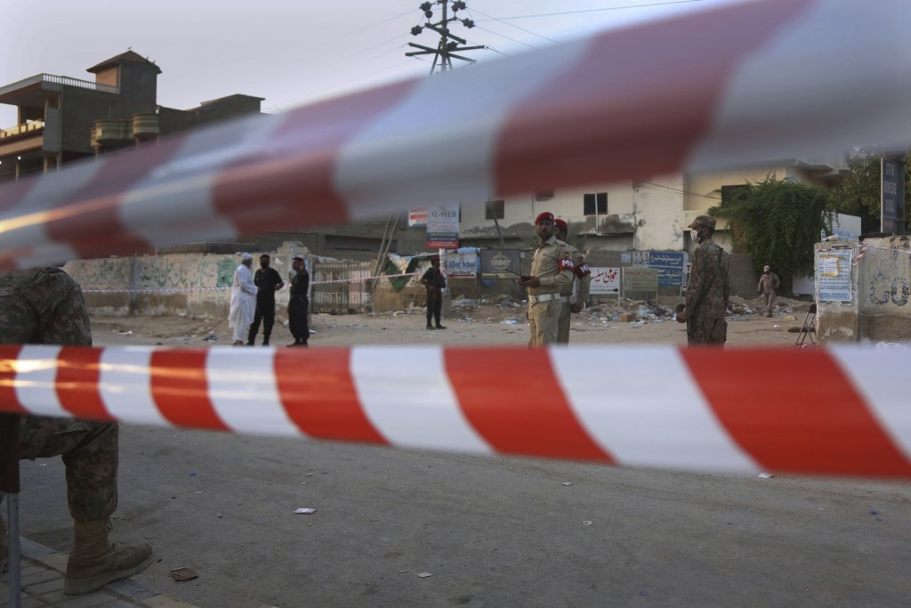 Pakistan army soldiers and police commandos stand guard while they cordon off a street leading to the site of a plane crash, in Karachi, Pakistan, Sat...