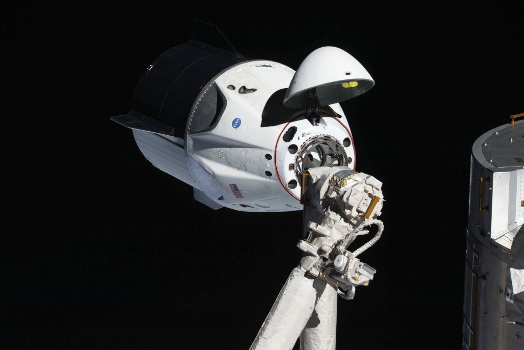In this March 4, 2019 photo made available by NASA, the uncrewed SpaceX Crew Dragon spacecraft, with its nose cone open to expose the docking mechanis...