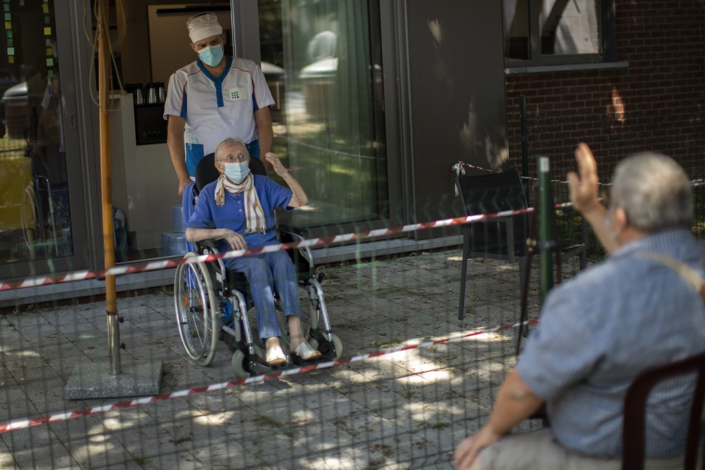Liliana Van Dyck, 85, keeping social distance to protect against the COVID-19 coronavirus, says goodbye to her son, Marc, at the end of his visit duri...