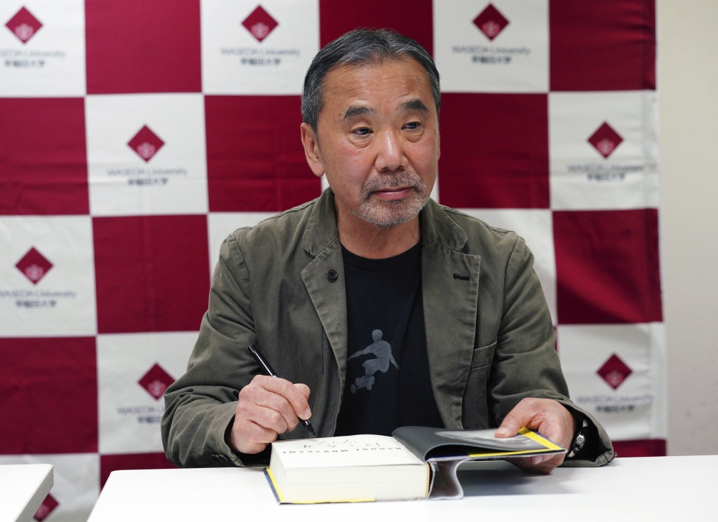 "FILE - In this Nov. 3, 2018, file photo, Japanese novelist Haruki Murakami signs his autograph on his novel ""Killing Commendatore"" during a press conf..."
