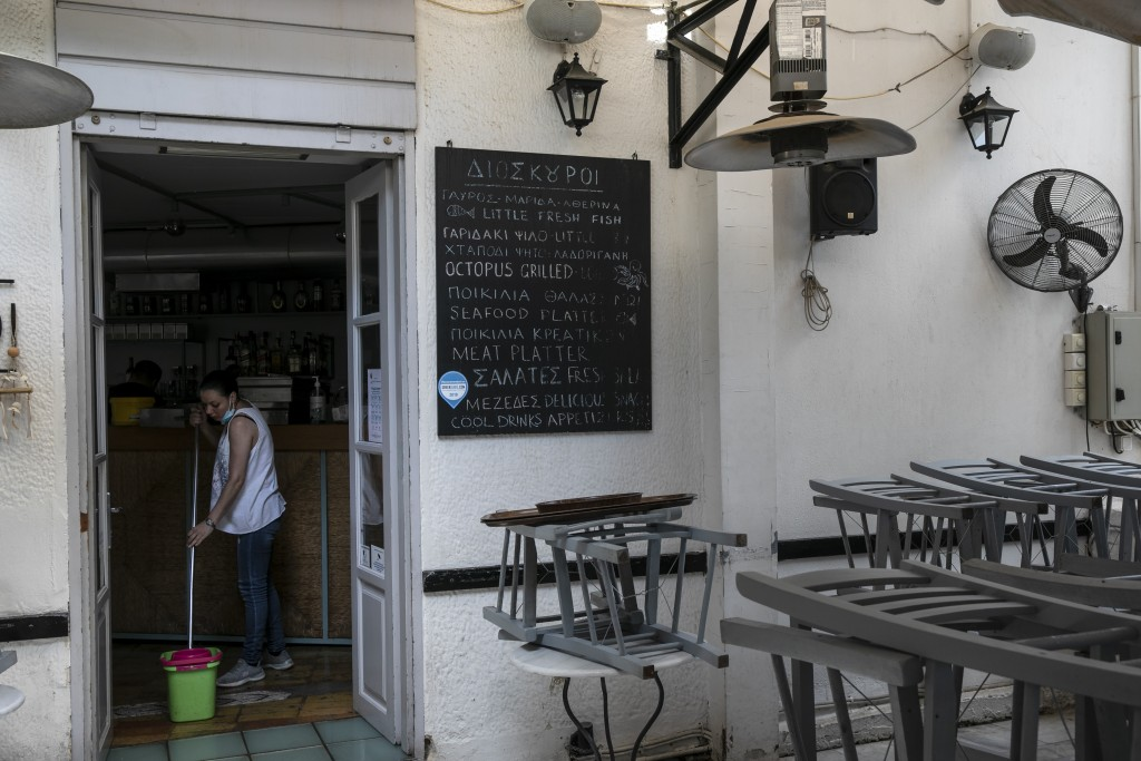 A woman mops the floor of a tavern being prepared for reopening, in Athens, Saturday, May 23, 2020. Restaurants and cafes are allowed to reopen on Mon...