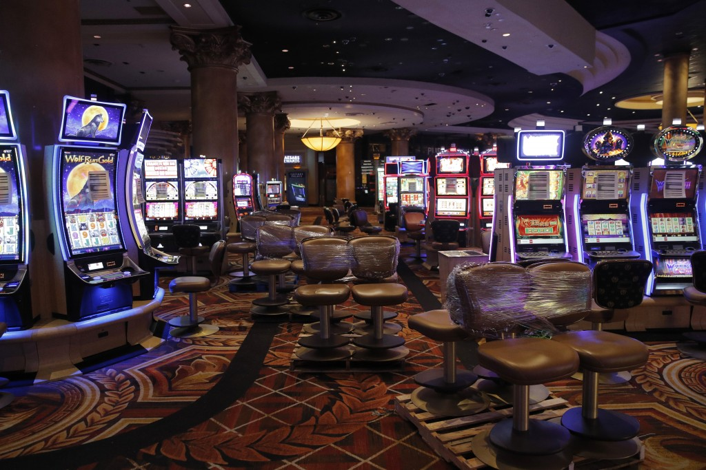 Chairs sit on pallets as some are being removed from electronic slot machines to maintain social distancing between players at a closed Caesars Palace...