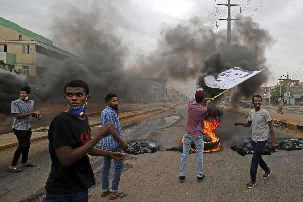 Sudanese men burn tyres during a demonstration to commemorate the first anniversary of a deadly crackdown carried out by security forces on protesters...