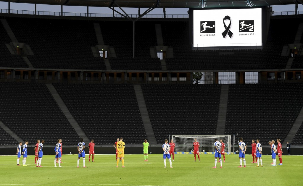 Players observe a minute's silence to commemorate the victims of the coronavirus pandemic prior to the German Bundesliga soccer match between Hertha B...