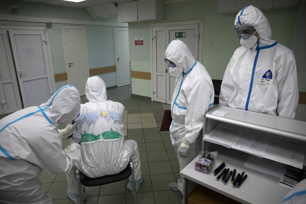 In this photo taken on Saturday, May 16, 2020, Dr. Osman Osmanov waits as a medical worker paints his protective gear during a rest on his shift at th...