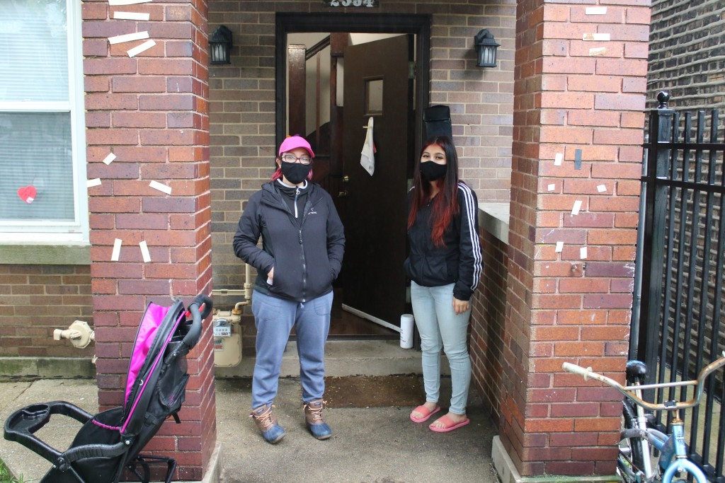 In this May 14, 2020 photo, Erendira Martinez and her daughter stand outside their home in the Little Village neighborhood of Chicago.  Chicago's Litt...