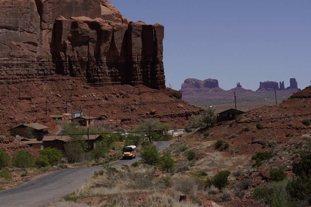 In this April 27, 2020, photo, a school bus is driven through Oljato-Monument Valley, Utah, on the Navajo reservation. Even before the pandemic, peopl...