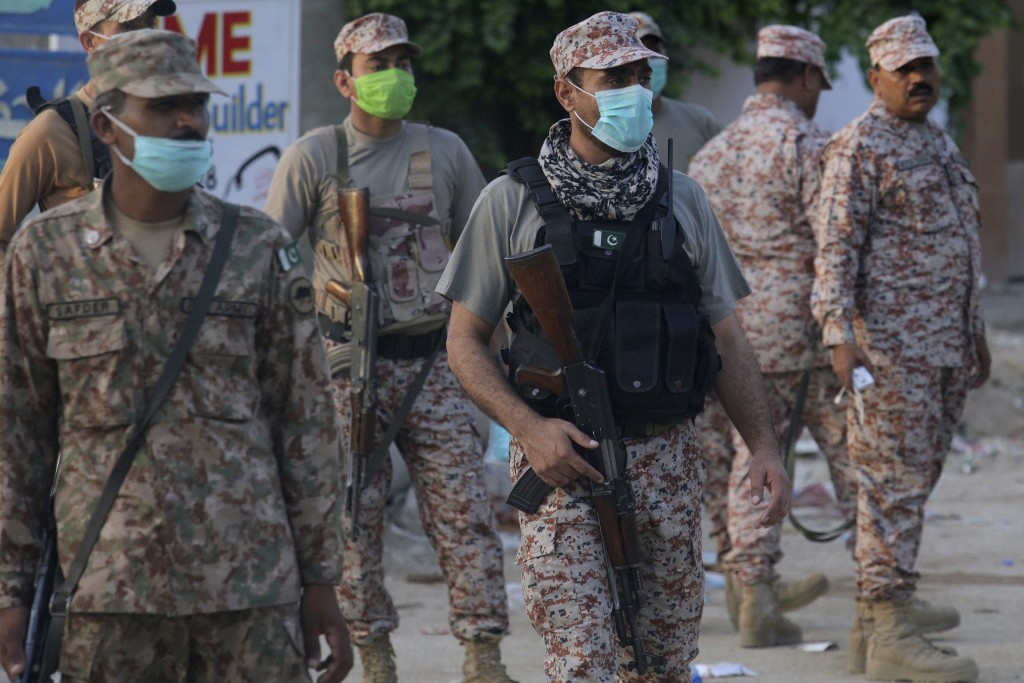Pakistan army soldiers stand guard while they cordon off a street leading to the site of a plane crash, in Karachi, Pakistan, Saturday, May 23, 2020. ...