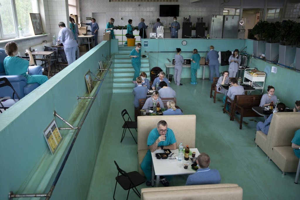 In this photo taken on Friday, May 15, 2020, Dr. Osman Osmanov, center, has breakfast before his shift at an intensive care unit of the Filatov City C...