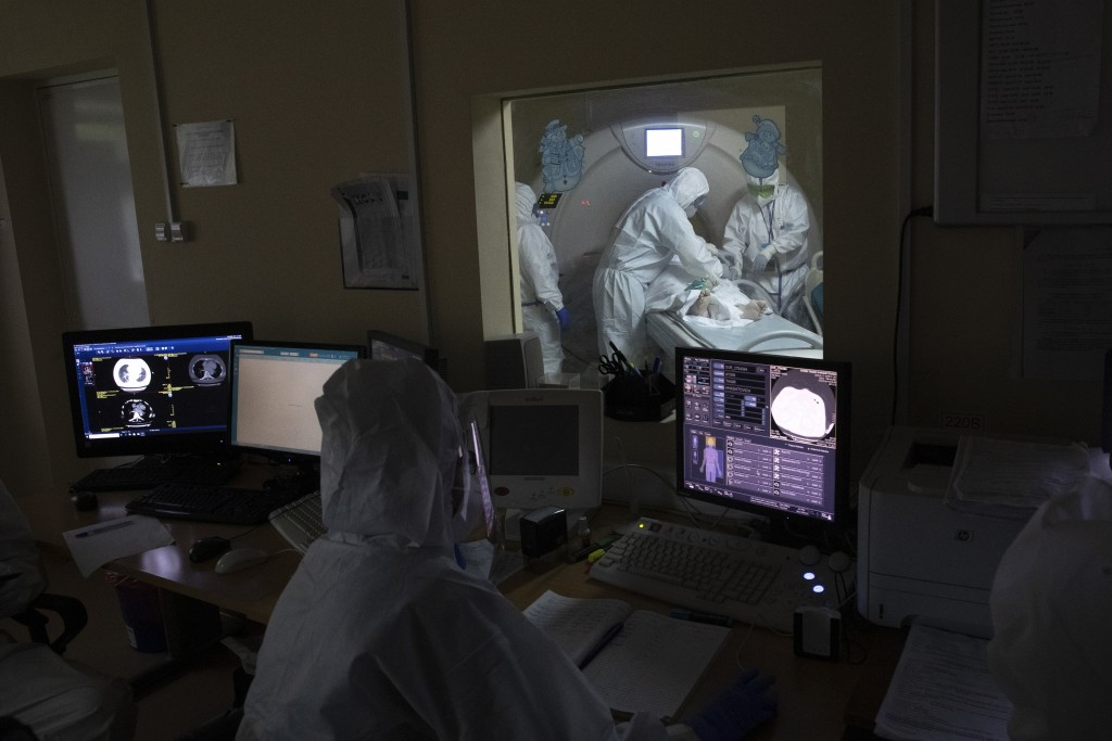 In this photo taken on Friday, May 15, 2020, Dr. Osman Osmanov, center, and Dr. Vitaly Mushkin, right, prepare a coronavirus patient on artificial lun...