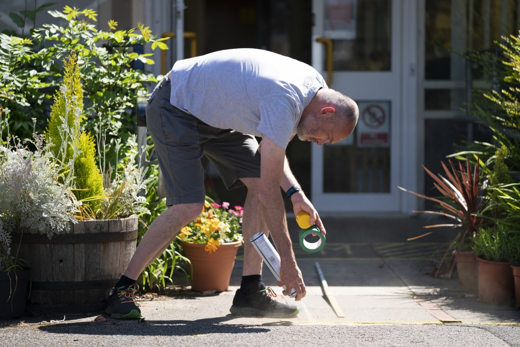David Waugh, head teacher at Poynton High School and Education Trust Leader sprays safe distance markers on the ground as measures are taken to preven...
