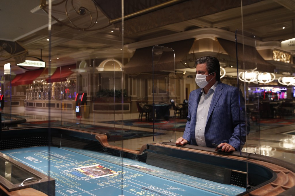 Bill Hornbuckle, acting CEO and president of MGM Resorts International, stands between acrylic barriers used as a coronavirus safety precaution at a c...