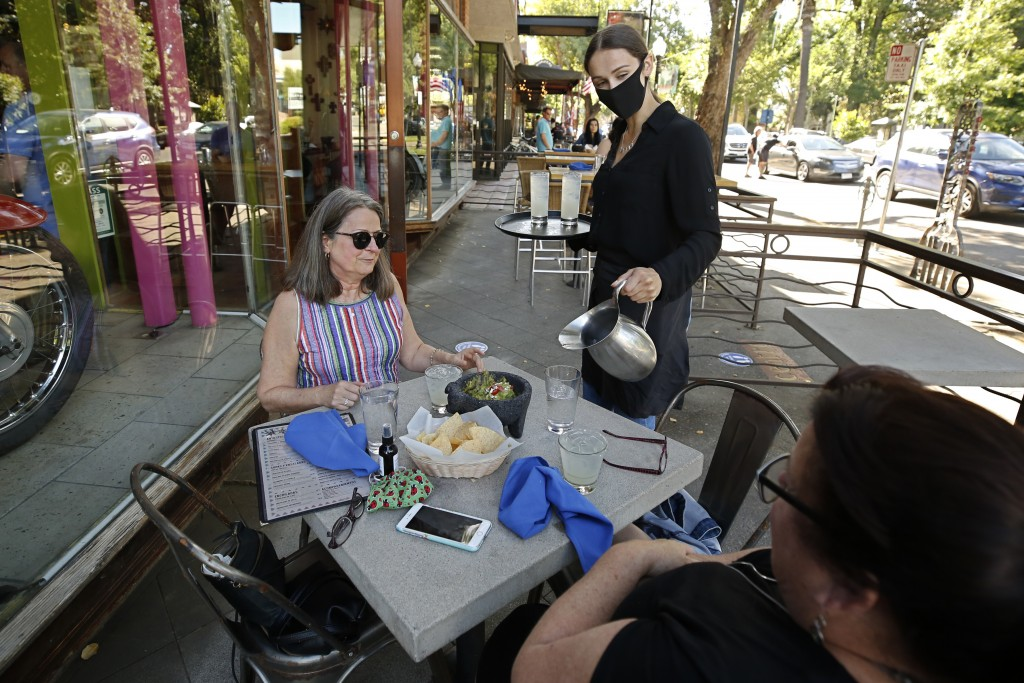 Delaney Thayer wears a face mask as she serves diners Jennifer Allen, left, and Julie Steacy at Centro Cocina Mexicana restaurant in Sacramento, Calif...