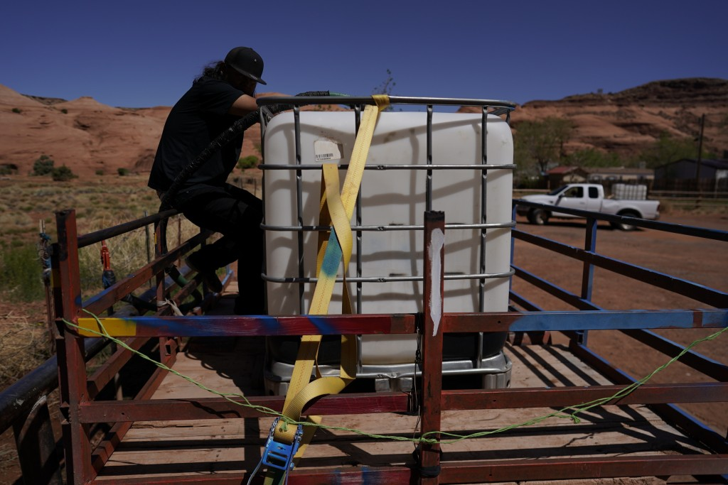 In this April 27, 2020, photo, Chris Topher Chee waits for water to fill a tank in the back of his truck to haul home in Oljato-Monument Valley, Utah,...