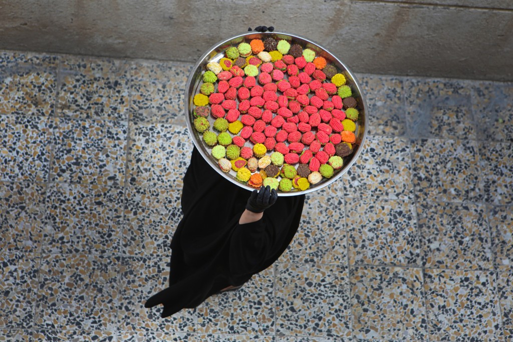An Iraqi women carries cookies for the upcoming Muslim Eid al- Fitr celebrations, that marks the end of the Muslim holy fasting month of Ramadan, in B...