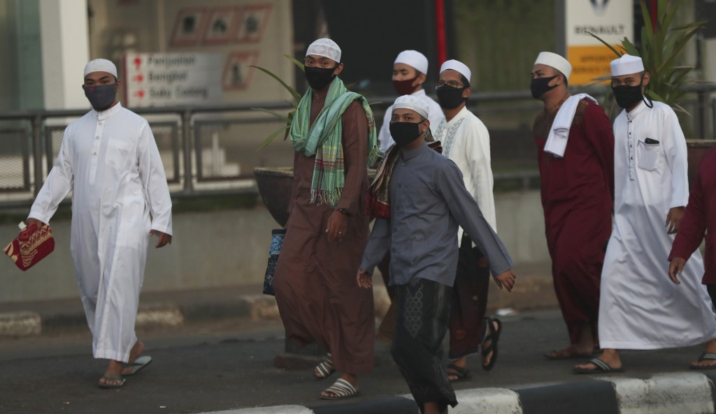 Indonesian Muslims wearing face masks walk to attend an Eid al-Fitr prayer that marks the end of the holy fasting month of Ramadan amid fears of the n...