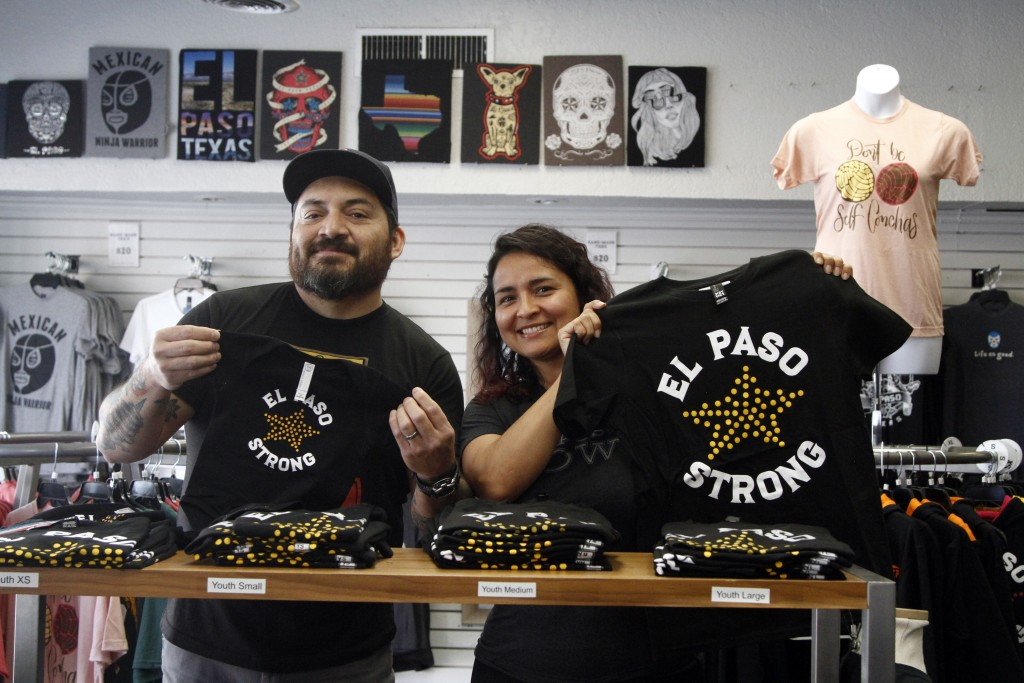 "In this Thursday, May 21, 2020 photo, artists Charlie Monarrez, 46, and Monica Monarrez, 36, hold up ""El Paso Strong"" clothing at the print shop where..."