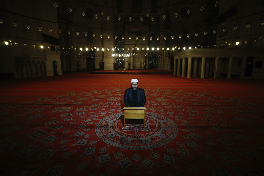 An Imam recites verses of the Qoran during the Eid al-Fitr prayer amid concerns of the coronavirus outbreak at the historical Suleymaniye Mosque in Is...