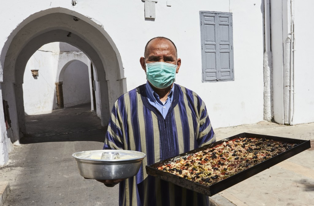 A man carries his cakes to the neighborhood oven in the old Habous district, in Casablanca, Morocco, Saturday 23 May 2020. As Eid AL Fitr approaches, ...