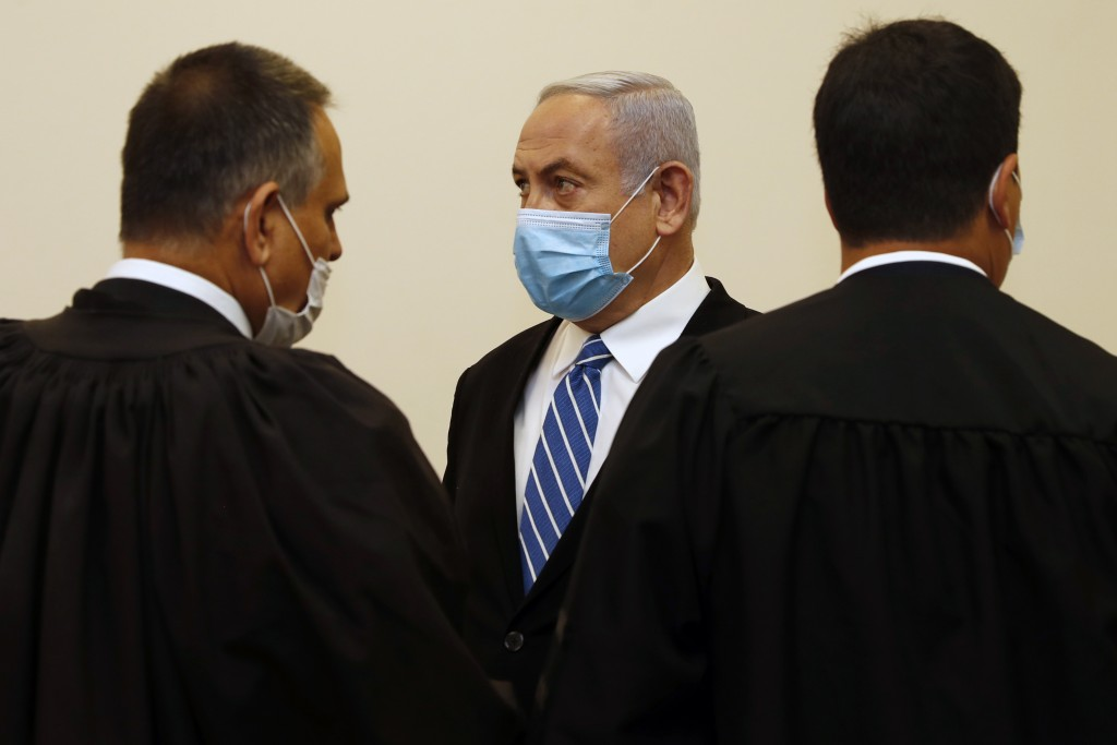 Israeli Prime Minister Benjamin Netanyahu, center, wearing a face mask in line with public health restrictions due to the coronavirus pandemic, stands...