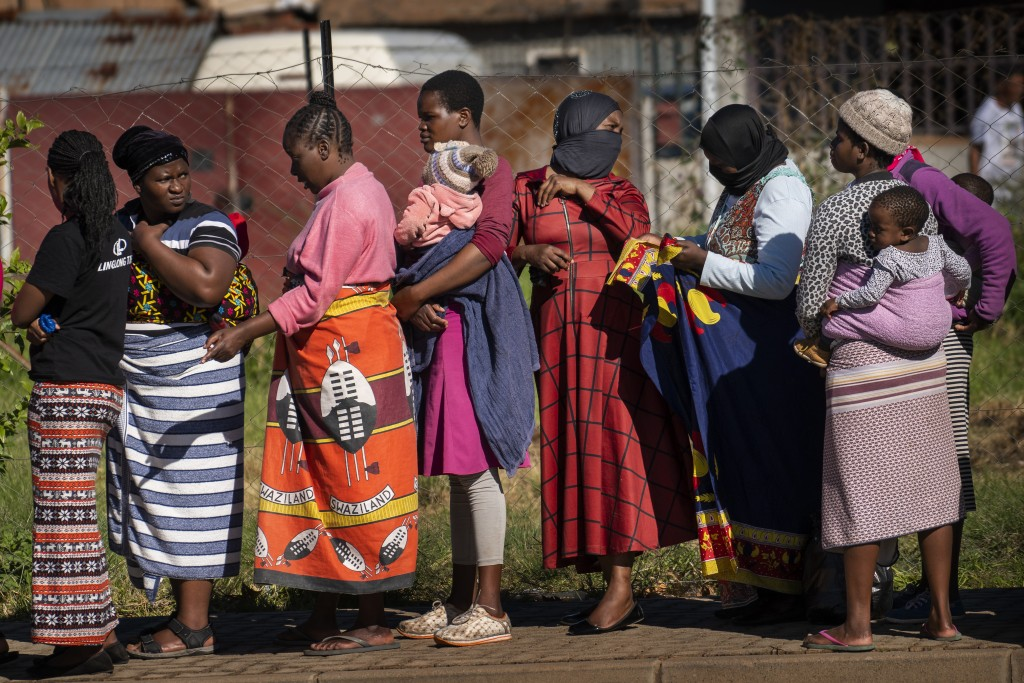FILE- In this file photo taken Thursday, April 30, 2020, Women carrying their children lineup to receive vegetables from the Jan Hofmeyer community se...