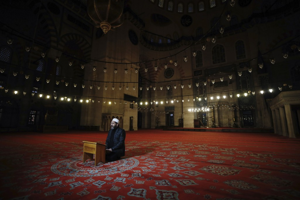 An imam recites Qoran during the Eid al-Fitr prayer amid concerns of the coronavirus outbreak at historical Suleymaniye Mosque, in Istanbul, early Sun...