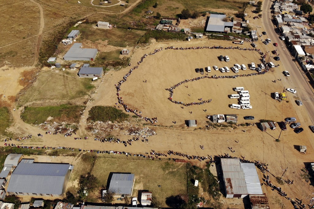 FILE- In this drone file photo taken Saturday May 2, 2020, thousands line up to receive food handouts in the Olievenhoutbos township of Midrand, South...