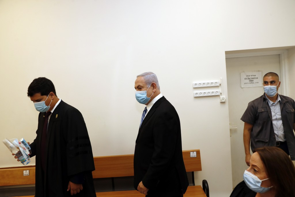 Israeli Prime Minister Benjamin Netanyahu, center, wearing a face mask in line with public health restrictions due to the coronavirus pandemic, enters...