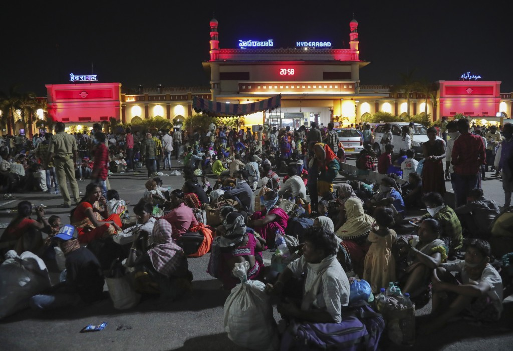 Migrant workers line up to board trains to their home states, at Hyderabad Railway Station in Hyderabad, India, Saturday, May 23, 2020. India's lockdo...