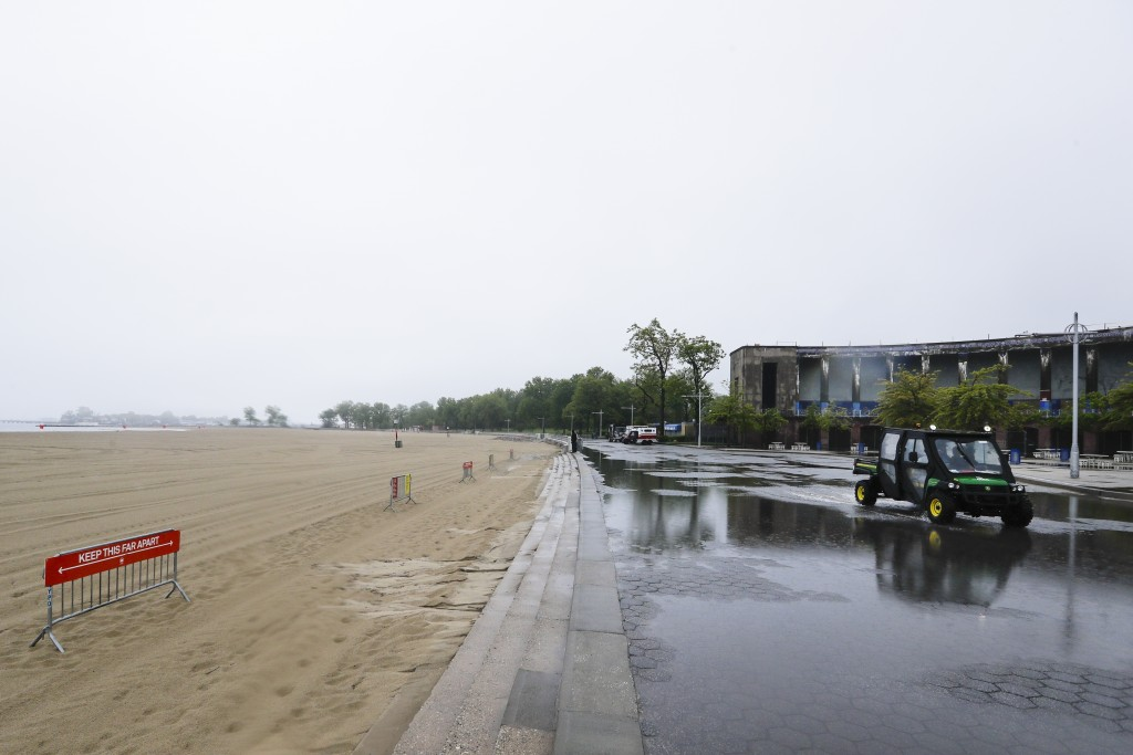 New York City Parks officials work at an empty Orchard Beach Saturday, May 23, 2020, in the Bronx borough of New York. Gov. Andrew Cuomo has given New...
